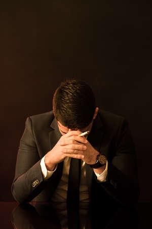 broken down: Broken down young businessman with cigarette