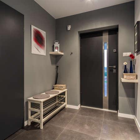 Gezellige hal met voordeur en grijs decor Stockfoto