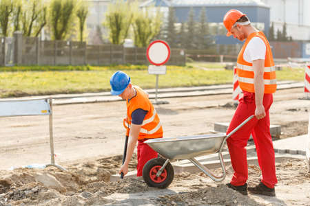 kerb: Photo of construction workers working together on building platform