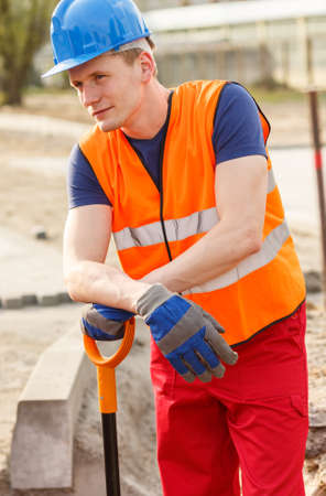 blue collar: Portrait of tired blue collar worker standing with shovel