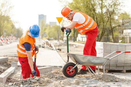 Picture of strong labourers digging on road construction