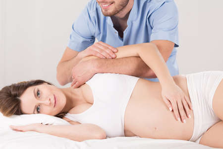 Pregnant woman having massage for health and for relax, light interior.