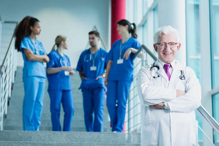 traineeship: Doctor in white uniform with stethoscope, in the background group of students in blue uniforms standing on stairs Stock Photo
