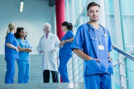 uniformes: Estudiante de medicina en azul uniforme con el estetoscopio, en el fondo médico permanente con el grupo de estudiantes Foto de archivo