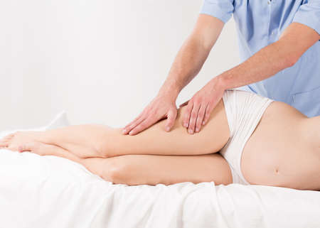 lymphatic drainage: Pregnant woman having professional therapeutic legs massage, white interior.