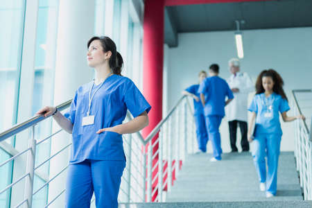 trainees: Student of medicine in blue uniform standing on stairs, in the background medic and trainees in uniforms