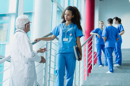 Doctor and medicine student talking on hospital stairs, in the background group of trainees in blue uniforms Reklamní fotografie