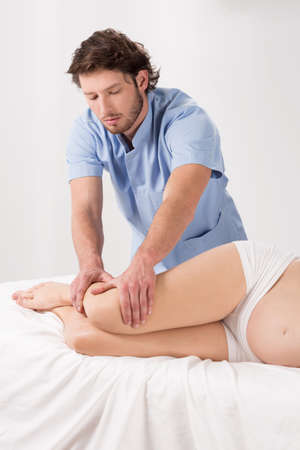 lymphatic drainage: Physiotherapist massaging pregnant womans legs, white interior. Stock Photo