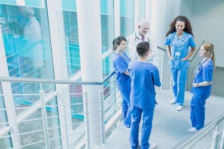 grupo de médicos: Grupo de estudiantes con uniformes azules que se colocan en las escaleras con el médico maduro en uniforme blanco
