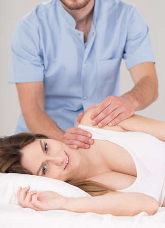 lymphatic drainage: Pregnant woman during professional massage, white interior.