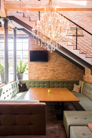 couches: Big table and couches under stairs in restaurant Stock Photo