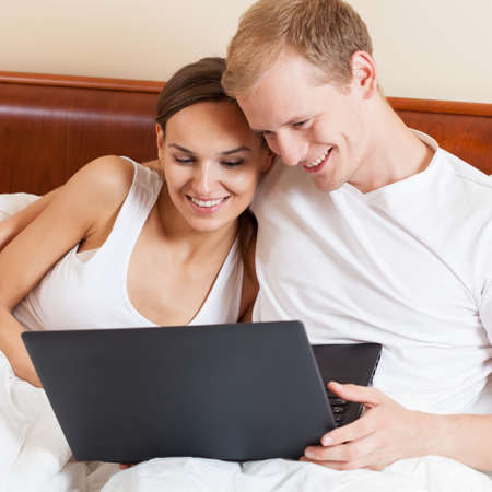 work addicted: View of couple with laptop in bed