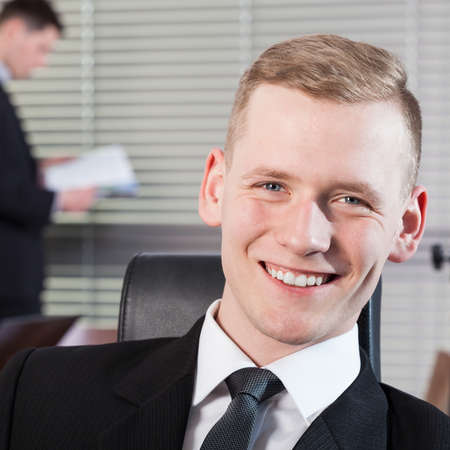 open minded: Smiling businessman and his co-workers during work