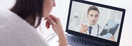 Concerned young doctor on video conference with patient. Looking at woman's xray photo