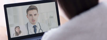 Young professional doctor giving advise to his young patient online on video conference Stock Photo