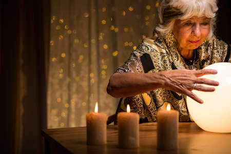 fortuneteller: Eccentric old woman looking into crystal ball