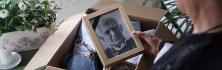 grieve: Widow packing and looking at photo of her dead husband
