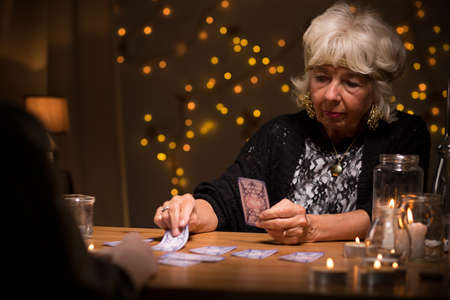 clairvoyant: Eccentric elderly woman reading magic tarot cards