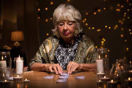 astrologist: Fortune teller reading tarot cards to predict fate