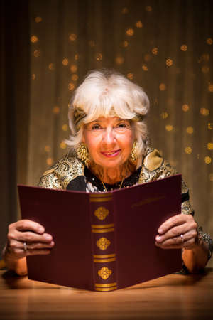 trickster: Smiling elderly fortune teller with magic spellbook Stock Photo