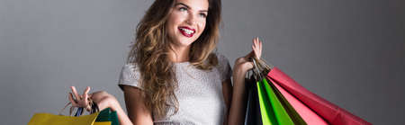 Young pretty happy woman after successful shopping with hands full of shopping bags