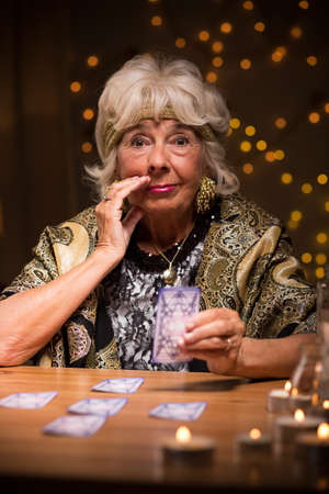 telepathy cards: Eccentric mysterious elderly lady with tarot cards Stock Photo