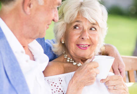 tenderness: Senior man embracing his wife with tenderness Stock Photo