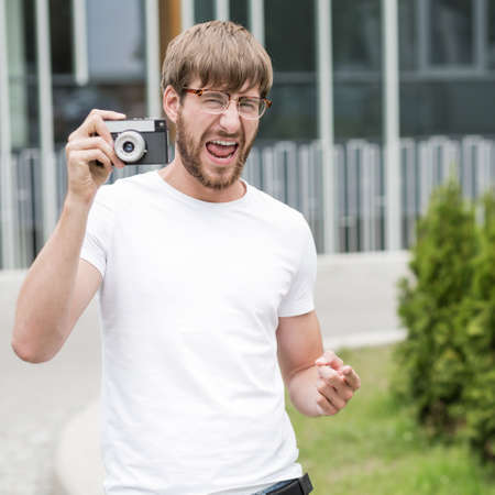 recollection: Happy young man holding camera and pointing