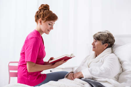 carer: Picture of young carer with old ill patient Stock Photo