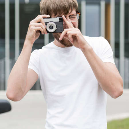 photography session: Young man in white shirt is taking photo Stock Photo