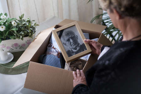 memories: Woman is packing things of her dead husband Stock Photo
