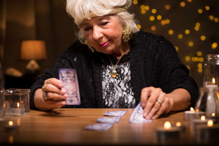 telepathy cards: Old woman predicting future from tarot cards Stock Photo