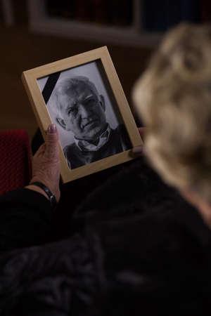 未亡人は悲しいことに彼女の死んだ夫の画像を探しています。 写真素材