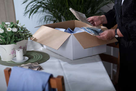put away: Old widow is saying goodbye to all her husbands things Stock Photo