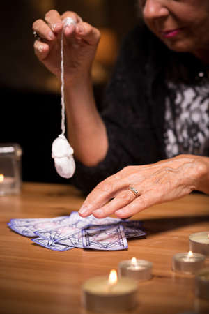 astrologist: Fortuneteller using a pendulum and tarot cards