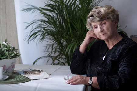 Bejaarde vrouw rouwt om haar overleden man