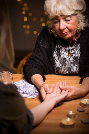 palm reading: Fortuneteller predicting future by reading somebodys palm