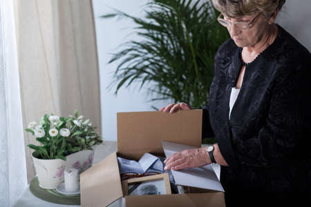 grieving: Widow is closing box with things of her husband Stock Photo