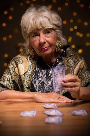 señora mayor: Mujer mayor con las cartas del tarot predecir el futuro