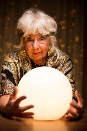 Fortuneteller looking into magic crystal ball to see the future