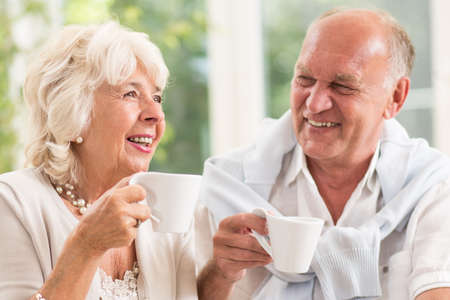Happy elderly married people smiling and drinking coffee