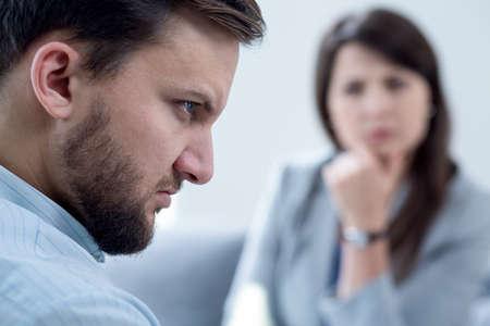 enfado: Hombre joven con la ira interna sobre la psicoterapia