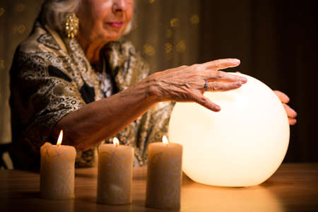 Woman with her hands on lighted crystal ball