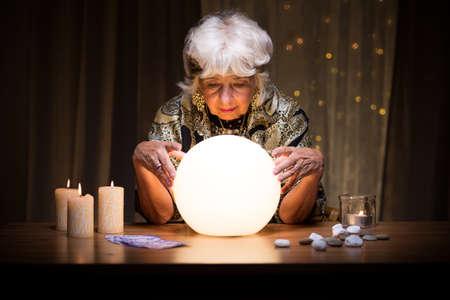 Vrouwelijke medium zit met magische kristallen bol