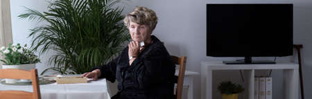 mourn: Widow sitting alone is thinking about her passed husband Stock Photo