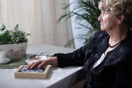 Une femme âgée tient sa main sur la photo du mari Banque d'images