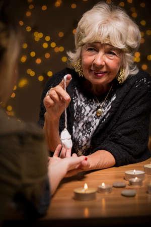 astrologist: Fortune teller predicting future with a pendulum