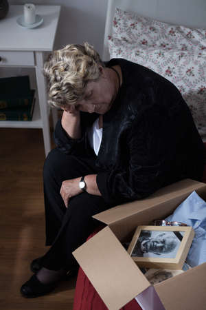 depressed: Widow is looking at box with her husband things