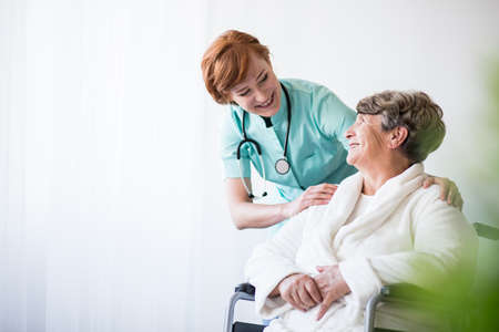 medical professional: Photo of positive doctor and patient on wheelchair