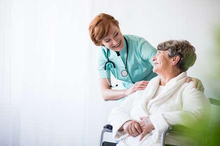 Foto del medico positivo e paziente sulla sedia a rotelle